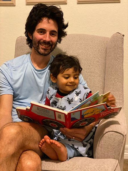 Nikhil shares a book with his dad (and Connie's son) Phill