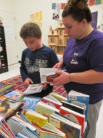 mother selecting books with her son